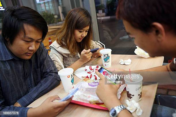 Htet Wai Than Htay left Aye Myat Thu center and Myat Thiha use their mobile phones as they sit inside a Lotteria Co restaurant at the Junction Square...