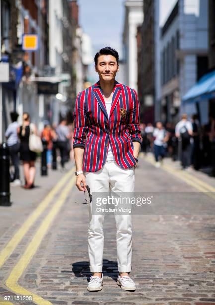 Hu Bing wearing striped blazer jacket white pants is seen during London Fashion Week Men's June 2018 on June 10 2018 in London England
