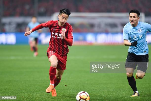 Hu Jinghang of Shanghai SIPG and Wang Liang of Dalian Yifang compete for the ball during the 2018 Chinese Football Association Super League first...
