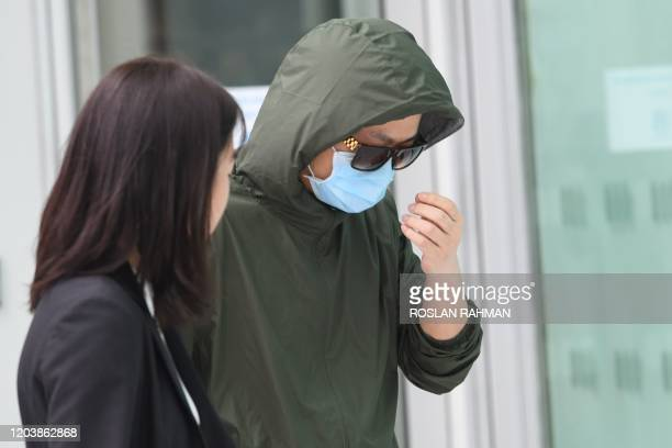 Hu Jun a Chinese national from Wuhan facing charges leaves the State Court in Singapore on February 28 2020 Hu Jun who was infected with coronavirus...
