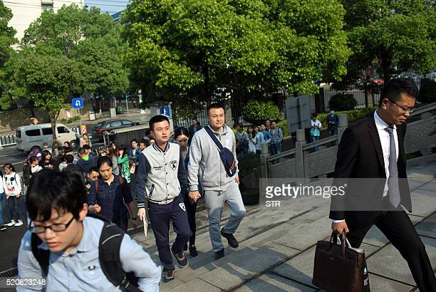 Hu Mingliang and his partner Sun Wenlin arrive at the People's Court of Furong District in Changsha central China's Hunan province on April 13 2016 A...