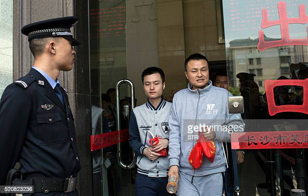 Hu Mingliang and his partner Sun Wenlin leave the People's Court of Furong District in Changsha central China's Hunan province on April 13 2016 A...