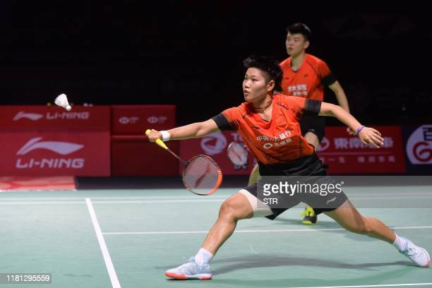 Huang Dongping of China hits a return beside partner Wang Yilyu against compatriot Zheng Siwei and Huang Yaqiong during their mixed doubles final...