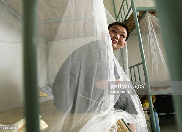 Huang Jiaxin a Chinese boy who successfully lost 60 kilograms of weight sits on a bed during a weightlosing summer camp organized by the Aimin...