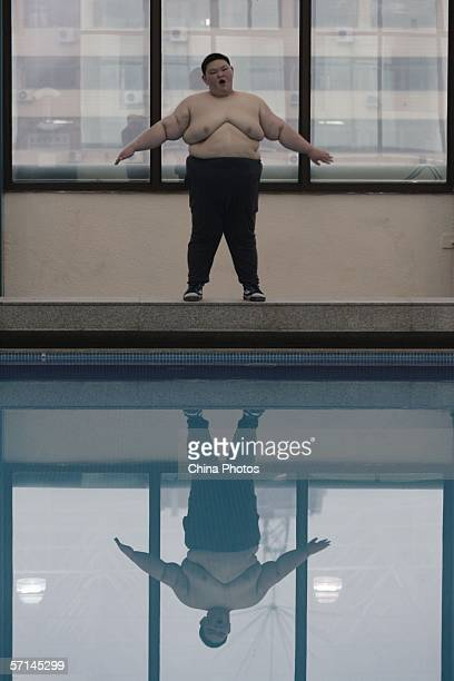 Huang Jiaxin fifteenyearsold performs weight reducing exercise next to a swimming pool of the Aimin Slimming Centre on March 21 2006 in Wuhan of...