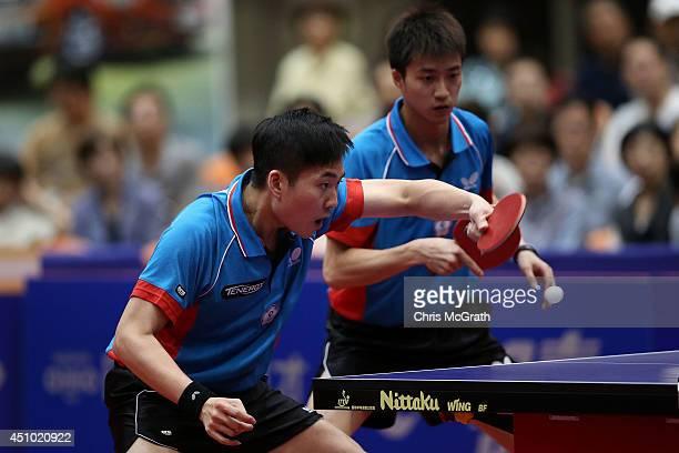 Huang Sheng-Sheng of Taipei returns a shot as team mate Chiang Hung-Chieh of Taipei watches on against Jun Mizutani and Kishikawa Seiya of Japan...