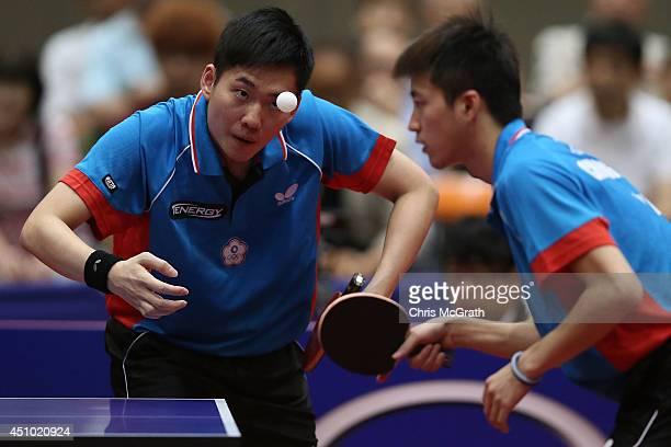 Huang Sheng-Sheng of Taipei serves as team mate Chiang Hung-Chieh of Taipei watches on against Jun Mizutani and Kishikawa Seiya of Japan during the...