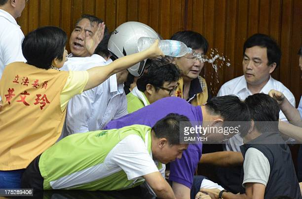 Huang Wenling a legislator from the main opposition Taiwan Solidarity Union pours water during a scuffle before a vote is taken on whether to build a...