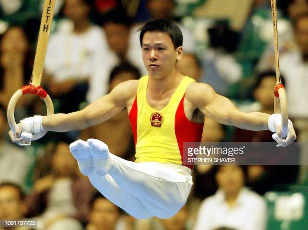 Huang Xu of China performs on the rings during the men's apparatus finals for the 14th Asian Games in Busan 04 October 2002 Huang finished in first...