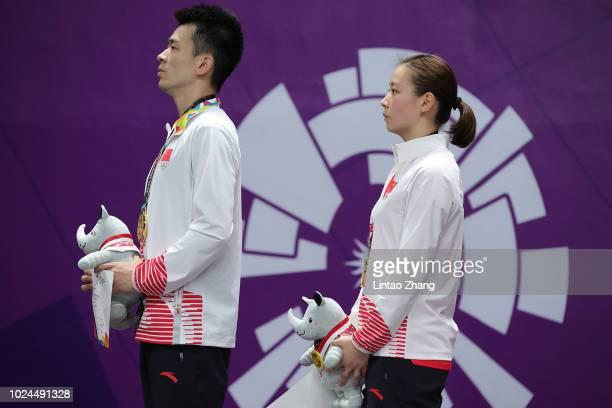 Huang Yaqiong and Zheng Siwei of China celebrate on the podium after winning Badminton mixed doubles final on day nine of the Asian Games on August...