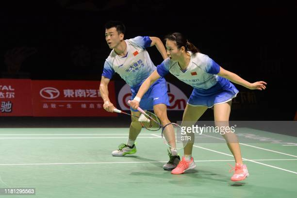 Huang Yaqiong of China hits a return beside partner Zheng Siwei against compatriot Wang Yilyu and Huang Dongping during their mixed doubles final...