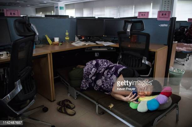Huawei employee watches a program on his smartphone as he rests at his cubicle during lunch break which is known to be common practice in many...
