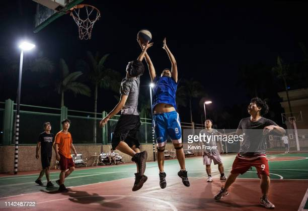 Huawei employees play basketball at a recreation area in staff housing at the end of the workday at the Bantian campus on April 25, 2019 in Shenzhen,...