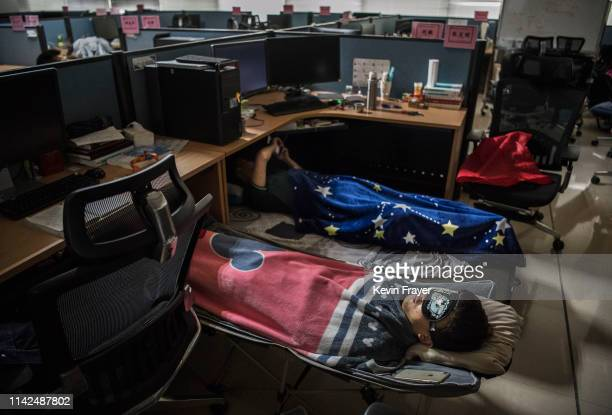 Huawei employees sleep at their cubicle during their lunch break which is known to be common practice in many workplaces in China at the research and...