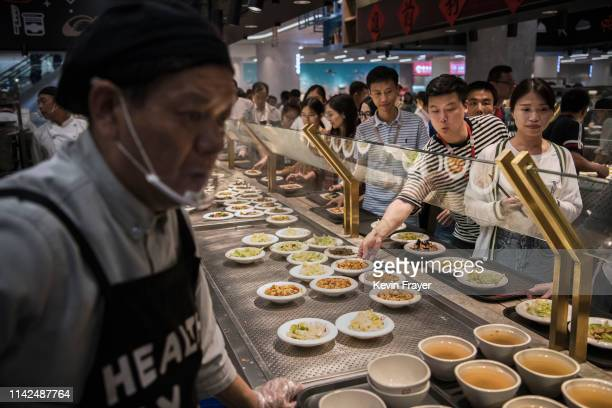 Huawei employees wait in line for lunch at a subsidized cafeteria at the company's Bantian campus on April 12 2019 in Shenzhen China Huawei is Chinas...