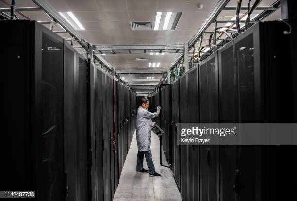 Huawei engineer opens the door a server unit to display during an organized tour at the Cyber Security Lab of the company's production campus on...