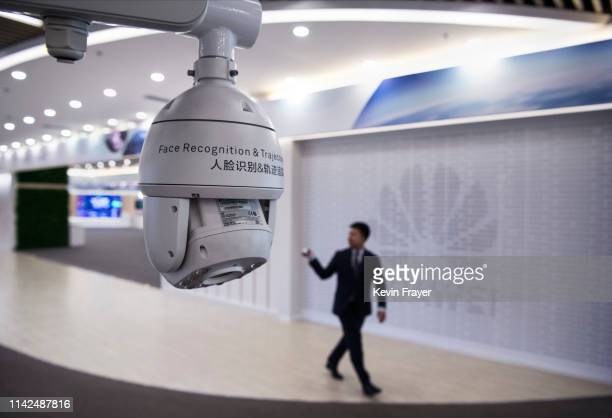 Huawei reception employee walks by a display for facial recognition cameras at the company's Bantian campus on April 26 2019 in Shenzhen ChinaHuawei...