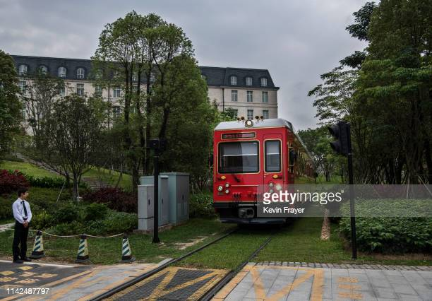 Huawei security guard stands at a crossing as a train used by employees clients and visitors passes by near the 'Paris Station' of the new sprawling...