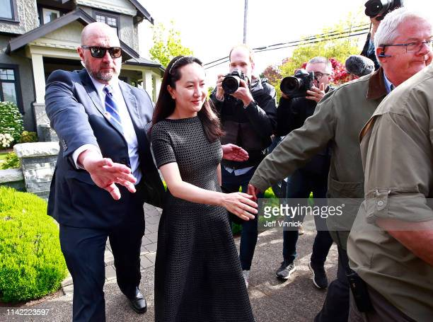 Huawei Technologies Chief Financial Officer Meng Wanzhou is escorted b y security as she leaves her home on May 8, 2019 in Vancouver, Canada. Wanzhou...
