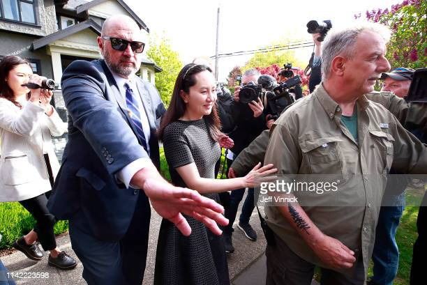 Huawei Technologies Chief Financial Officer Meng Wanzhou is escorted by security as she leaves her home on May 8, 2019 in Vancouver, Canada. Wanzhou...