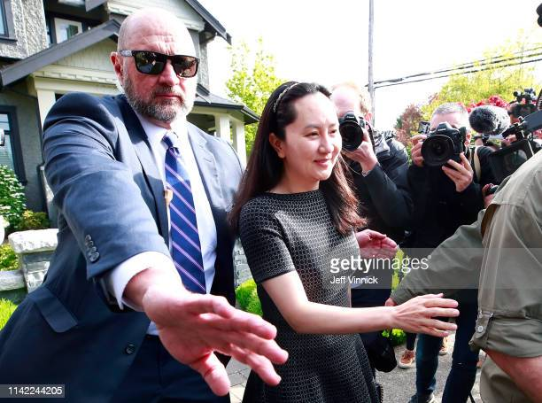 Huawei Technologies Chief Financial Officer Meng Wanzhou is escorted by security as she leaves her home on May 8 2019 in Vancouver Canada Wanzhou is...