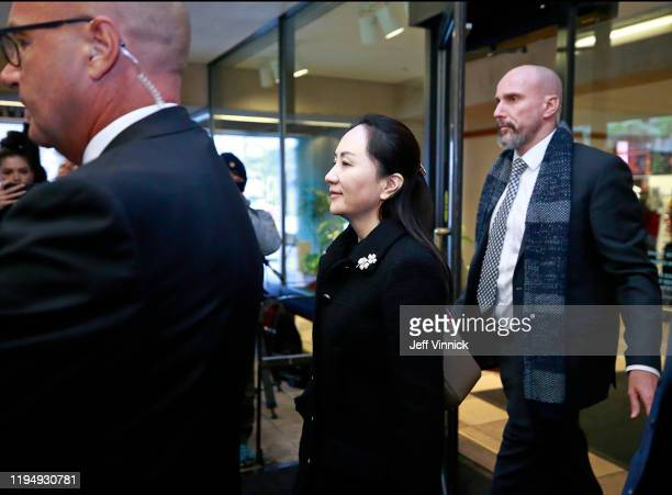 Huawei Technologies Chief Financial Officer Meng Wanzhou is escorted by her security personnel as she leaves court during a break for lunch on the...