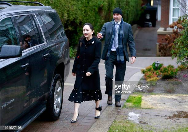 Huawei Technologies Chief Financial Officer Meng Wanzhou walks with her security personnel as she leaves her house on her way to a court appearance...