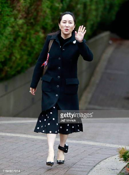 Huawei Technologies Chief Financial Officer Meng Wanzhou waves to the media as she leaves her house on her way to a court appearance on the first day...