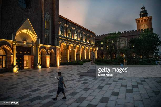 Huawei worker looks at t his smartphone as he walks at the sprawling 'Ox Horn' Research and Development campus on April 25 2019 in Dongguan near...