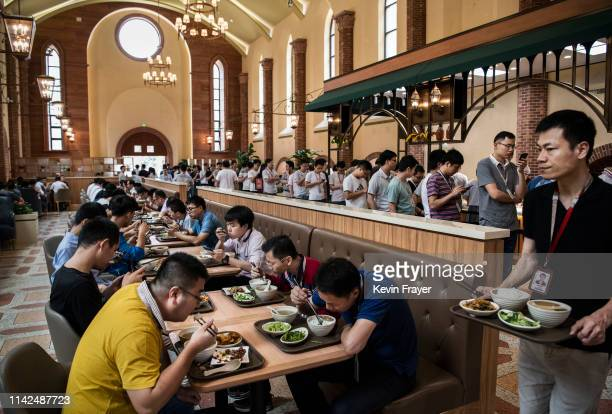 Huawei workers eat lunch as others lineup at one of many cafeterias serving subsidized food at the sprawling 'Ox Horn' Research and Development...