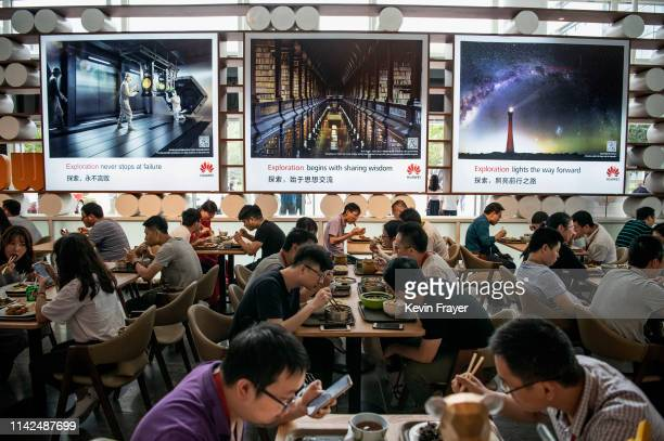 Huawei workers eat subsidized lunch in one of many large cafeterias at the company's Bantian campus on April 28 2019 in Shenzhen China Huawei is...