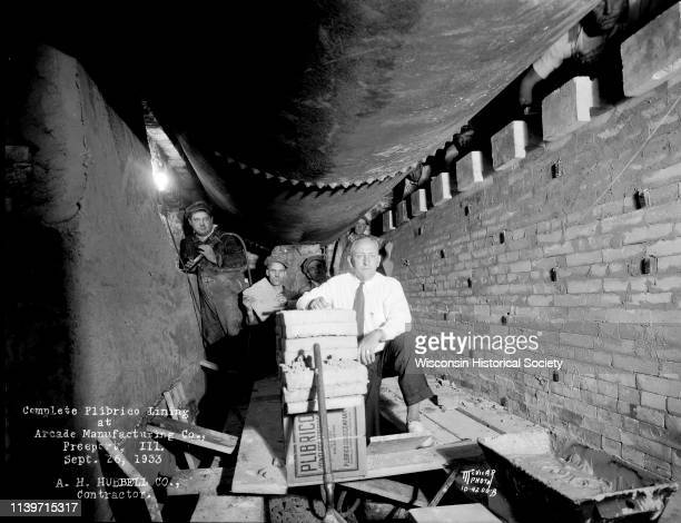 AH Hubbell Company workers build a 'Complete Plibrico Jointless Firebrick Lining' brick wall around a boiler in the engine room at Arcade...