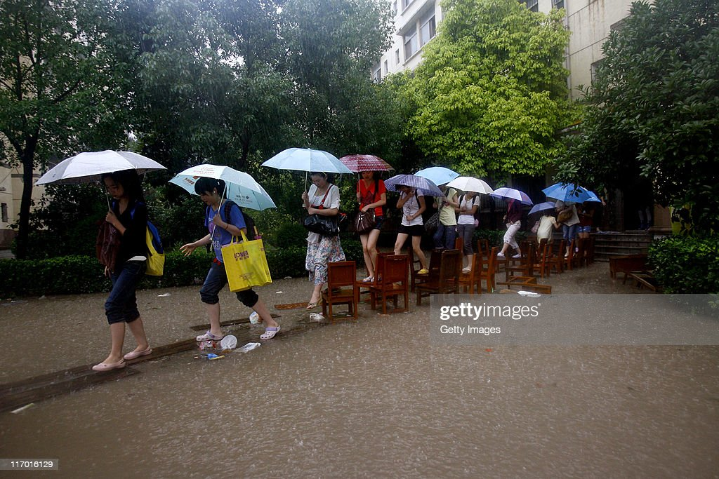 Hubei University students walk on a 'bridge' of chairs over a flooded path on June 18, 2011 in Wuhan, Hubei Province of China. A heavy rainstorm hit Wuhan on Saturday, causing flooding across the region.