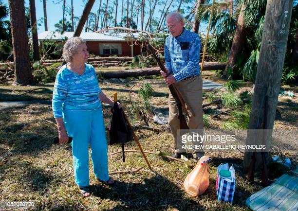 Hubert and Katrina Richards wait for family to pick them up as they carry family heirlooms near their damaged house in Port St Joe beach Florida on...