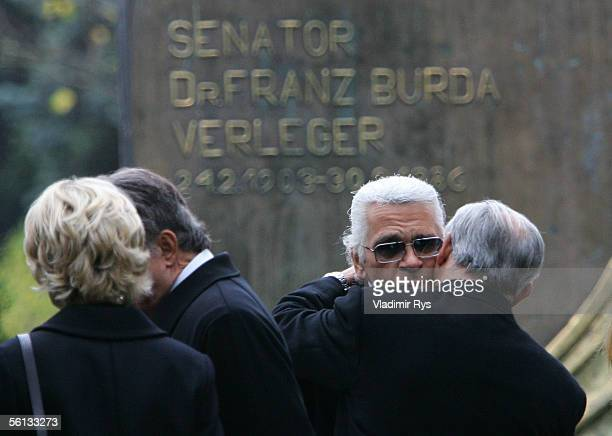 Hubert Burda hugs Karl Lagerfeld next to the grave of his mother Aenne Burda after her funeral service on November 10 2005 in Offenburg Germany Aenne...