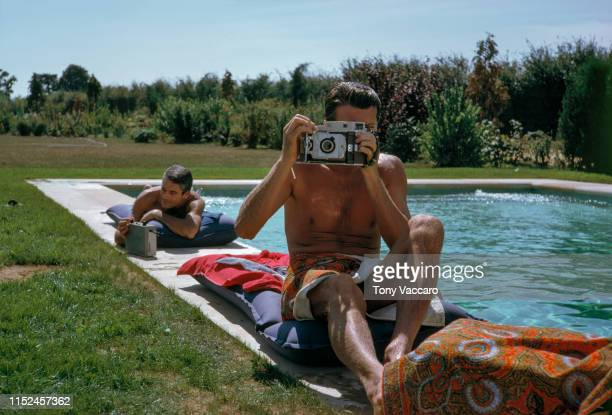 Hubert De Givenchy is sitting by the pool with Philippe Venet at his summer home. Hubert is holding a Polaroid camera and taking picture of Tony...