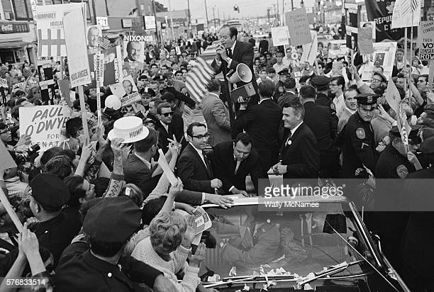 Hubert Humphrey speaks from a convertible as it moves down a street in Peoria Illinois during a rally for his presidential campaign Audience members...