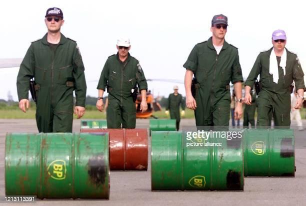 Hubschrauberpiloten des Bundesgrenzschutzes rollen am 832000 auf dem Flughafen der mosambikanischen Stadt Beira leere FlugbenzinKanister über das...
