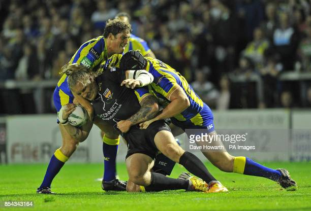 Huddersfield Giants' Eorl Crabtree is tackled by Warrington Wolves' Chris Hill and Ben Harrison during the Super League SemiFinal match at The...