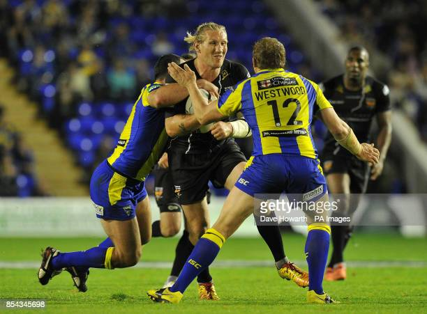 Huddersfield Giants' Eorl Crabtree is tackled by Warrington Wolves' Chris Hill and Warrington Wolves' Ben Westwood during the Super League SemiFinal...