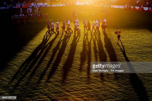 Huddersfield Giants players warm up during a sunset before the Betfred Super League match at the Totally Wicked Stadium St Helens