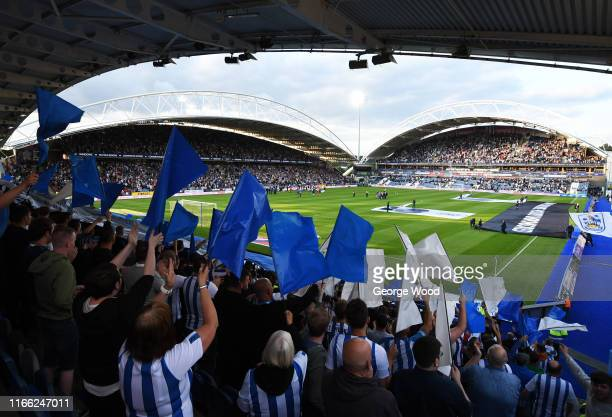 Huddersfield Town fans wave flags prior to the Sky Bet Championship match between Huddersfield Town and Derby County at John Smith's Stadium on...