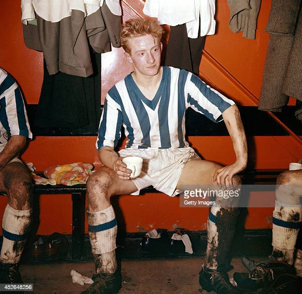 Huddersfield Town player Denis Law enjoys a cup of tea in the dressing room after a game in 1957 in England
