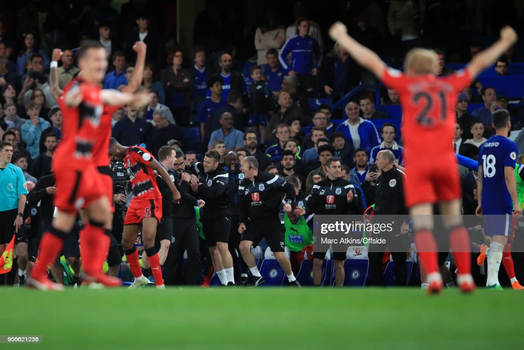 Huddersfield Town players and coaching staff react as they secure safety in the Premier League during the Premier League match between Chelsea and Huddersfield Town at Stamford Bridge on May 9, 2018 in London, England.
