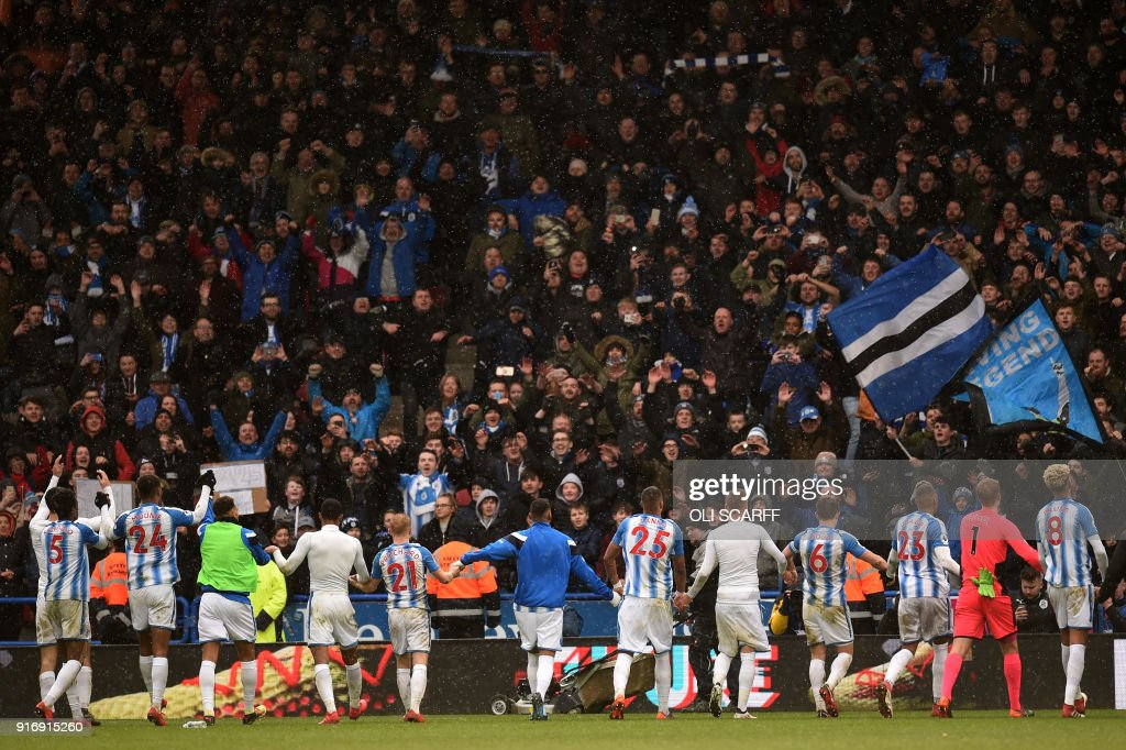 Huddersfield Town players celebrate victory during the English Premier League football match between Huddersfield Town and Bournemouth at the John Smith's stadium in Huddersfield, northern England on February 11, 2018. / AFP PHOTO / Oli SCARFF / RESTRICTED TO EDITORIAL USE. No use with unauthorized audio, video, data, fixture lists, club/league logos or 'live' services. Online in-match use limited to 75 images, no video emulation. No use in betting, games or single club/league/player publications. /