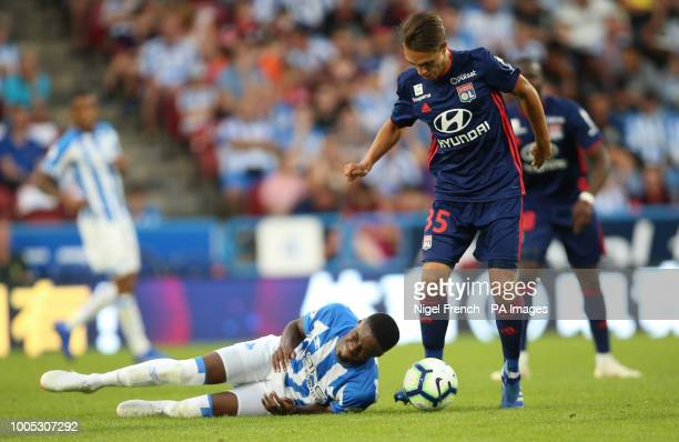 Huddersfield Town's Adama Diakhaby and Lyon's Maxence Caqueret battle for the ball during a preseason friendly match at the Kirklees Stadium...