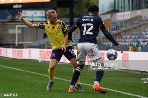 Huddersfield Town's Alex Pritchard battles for possession with Millwall's Mahlon Romeo during the Sky Bet Championship match between Millwall and...