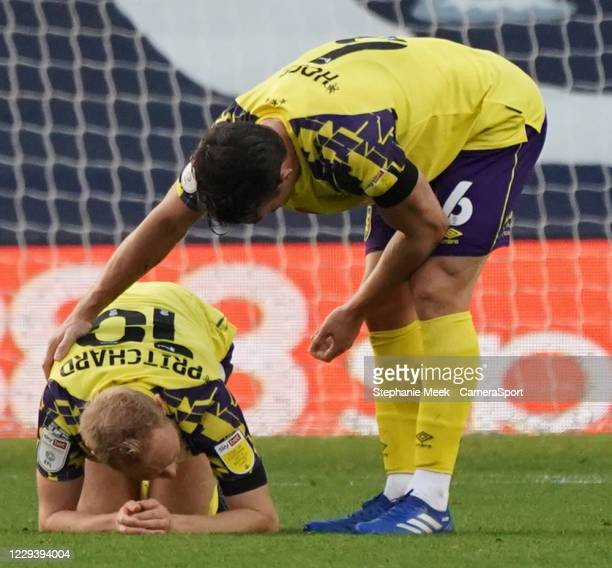 Huddersfield Town's Alex Pritchard comforted by teammate Jonathan Hogg during the Sky Bet Championship match between Millwall and Huddersfield Town...