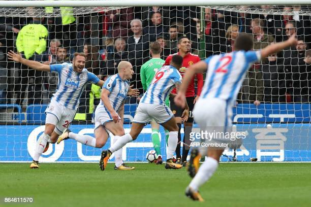 Huddersfield Town's Australian midfielder Aaron Mooy celebrates with teammates after scoring the opening goal of the English Premier League football...