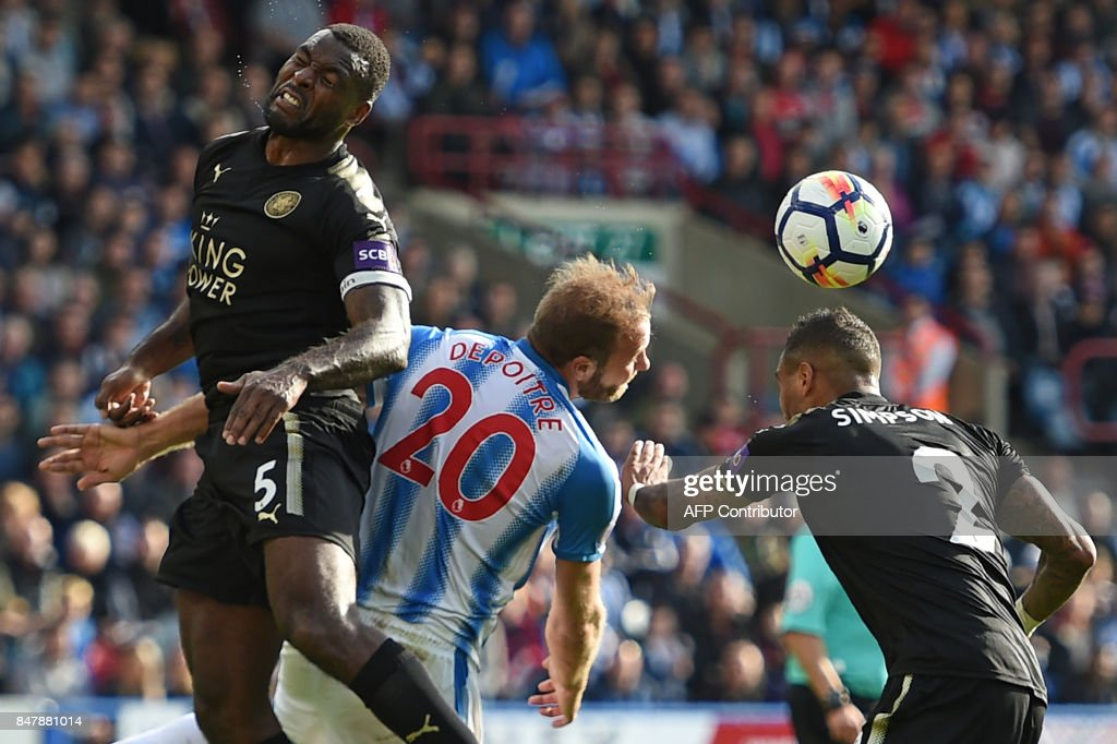 Huddersfield Town's Belgian striker Laurent Depoitre (C) vies with Leicester City's English-born Jamaican defender Wes Morgan (L) and Leicester City's English defender Danny Simpson (R) during the English Premier League football match between Huddersfield Town and Leicester City at the John Smith's stadium in Huddersfield, northern England on September 16, 2017. / AFP PHOTO / Oli SCARFF / RESTRICTED TO EDITORIAL USE. No use with unauthorized audio, video, data, fixture lists, club/league logos or 'live' services. Online in-match use limited to 75 images, no video emulation. No use in betting, games or single club/league/player publications. /
